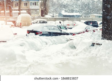Apartment or office building parking lot with many cars covered by snow stucked after heavy blizzard snowfall on winter day. Snowdrifts and freezed vehicles. Extreme weather conditions
