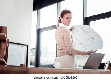 Apartment plan. Creative inspired young family woman feeling curious while showing her new apartment plan