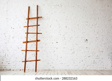 Apartment Renovation. Wooden Ladder near white Brick Wall in empty Room