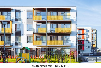 Apartment residential house facade architecture and children playground and outdoor facilities. Blue sky on background.