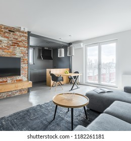 Apartment with simple living room with designed brick wall and open kitchen