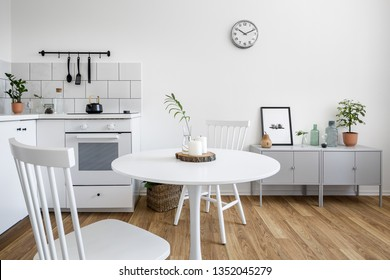 Apartment with two white chairs and round, wooden, white table