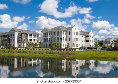 Apartments and Condos with reflection in a nearby lake and partly cloudy blue sky