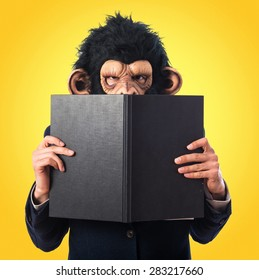 ape man hiding behind a book over colorful background
