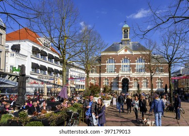 Apeldoorn, Holland, March 28, 2016: People enjoying a drink in the sun on the square in front of the old city hall in the center.