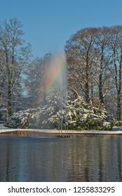 Apeldoorn, Netherlands - 2008-11-24 Oranjepark: rainbow fountain in a sunny snowy winter day with the water of the pond in the foreground.