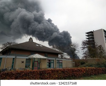 APELDOORN, THE NETHERLANDS - 27 NOVEMBER 2018: black smoke cloud above residential area. An extensive fire destroys a large building