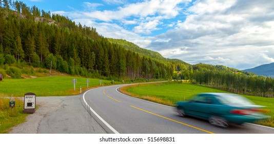 """Apent"" means ""Open"". Fast speed car driving motion blur on the highway road in green mountains landscape of Norway, Scandinavia, Europe."