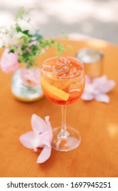 Aperitif alcoholic spritzer on orange background with pink flowers, bar cocktail with citrus, Italian aperitivo in Italy