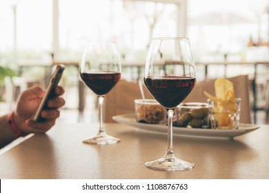 Aperitif with appetizer for two with 2 glasses of red wine - hand of a man distracted by social on his smartphone / mobile phone
