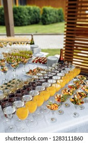 Aperitif. Festive table with glasses of various drinks and snacks. Juice, wine, champagne. Outdoors