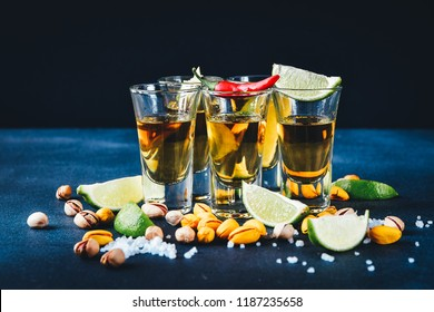 aperitif with friends in the bar, five glasses of alcohol with snacks lime and pistachio, salt and chili pepper for decoration. Tequila shots, vodka,whisky, rum.  selective focus and copy space
