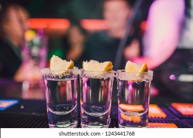 aperitif with friends in the bar, five glasses of alcohol with snacks lime and pistachio, salt and chili pepper for decoration. Tequila shots, vodka,whisky, rum. selective focus and copy space.
