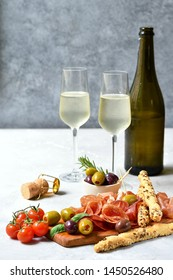 """aperitif in italian restaurant : appetizer  with prosciutto and salami, olives,  two glasses of white wine.  Menu traditional """"happy hour"""" in Italy a glass of Prosecco and snacks. selective focus"""
