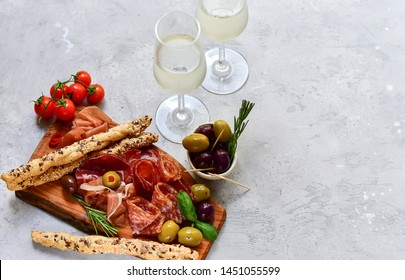 """aperitif in italian restaurant : appetizer  with prosciutto and salami, olives,  two glasses of white wine. Menu traditional """"happy hour"""" in Italy a glass of Prosecco and snacks. food flat lay"""