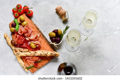 "aperitif in italian restaurant : appetizer  with prosciutto and salami, olives,  two glasses of white wine. Menu traditional ""happy hour"" in Italy a glass of Prosecco and snacks. food flat lay"