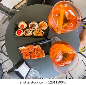 Aperitif on black bar table outdoor. Orange fruit drinks with ice, appetizers.