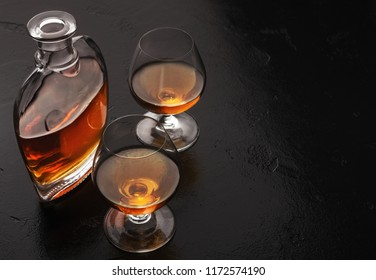 Aperitif at restaurant. Two glasses of brandy or cognac and bottle on black background, copy space