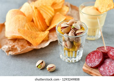 aperitif snacks at the bar: chips, nachos with sauce, pistachios and salami, aperitif, relax in the bar with friends, beer party.  selective focus and copy space