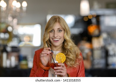 Aperitif time: Smiling young blonde girl enjoying her time drinking a cocktail in a bar towards the camera blurred background.
