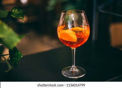 Aperol Spritz Cocktail in the Bar on the Dark Background with Green Plants, Free Space for Text