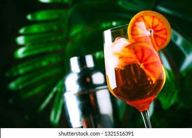 Aperol spritz cocktail in big wine glass with bloody oranges, summer Italian fresh alcohol cold drink. Wooden bar counter background with tools, summer mood concept with palm trees, selective focus