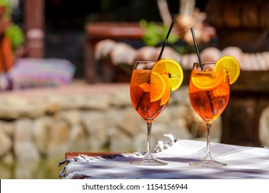 Aperol spritz cocktail in glass on the wooden table against a bright sunny cafe.