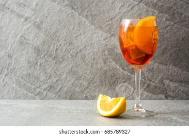 Aperol spritz cocktail in glass on gray stone