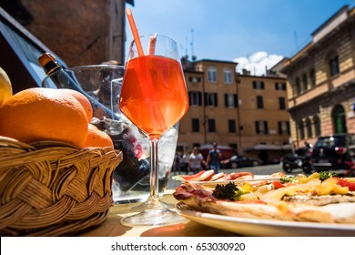 Aperol spritz cocktail and Italian pizza on a piazza Santa Maria in Trastevere. Rome . Italy