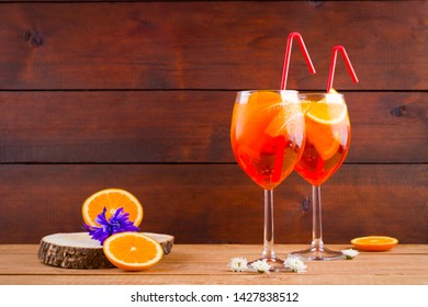 Aperol spritz cocktail on wooden boards. Summer alcoholic cocktail with orange slices and flowers. Aperol spritz on wooden boards