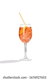 Aperol Spritz cocktail with a slice of orange, ice cubes and an orange straw is contained in a high glass on the long stem. The bright illustrative picture is made on the white background.