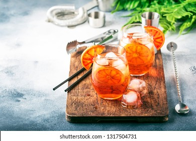 Aperol spritz cocktail in wine glass with sparkling wine, liqueur, ice cubes and red orange - summer Italian low alcohol cold drink, gray stone bar counter background with tools,  selective focus