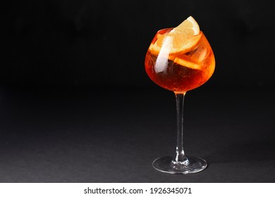 Aperol spritz in a glass with ice and orange on a black table, horizontal, space for text