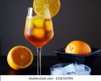 Aperol Spritz with ice and orange slices served in wine glass with condensation. Italian aperitif cocktail on black slate tray over dark background.