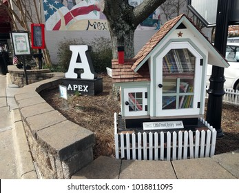APEX, NC / USA - APRIL 2015: Town sign on North Salem Street in Historic Apex, North Carolina (NC) with a mural in the background. The Little Free Library allows you to take a book if you leave a book