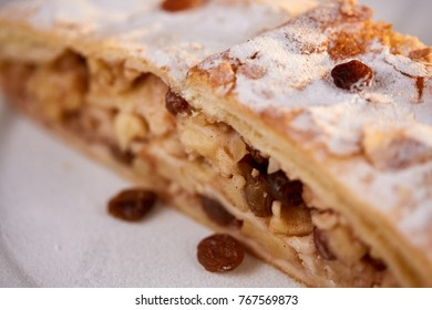 Apfelstrudel with raisins on a plate with apples on a table