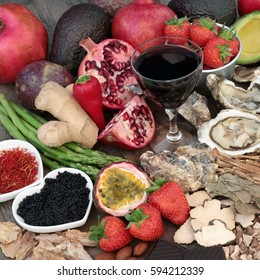 Aphrodisiac food and drink selection used to promote good sexual health forming a background.