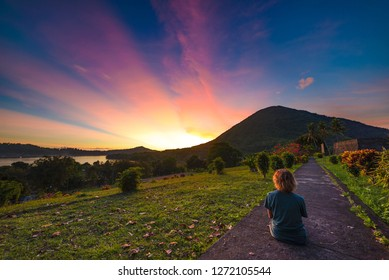 Api volcano at sunset, sitting woman looking at view from Banda Naira fort, Maluku Moluccas Indonesia, Top travel tourist destination, dramatic sky.