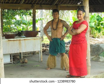 Apia / Samoa - 04 09 2016: polynesian woman and man in traditional samoan clothing standing in the fale (open wooden house) in Samoan Cultural Village, Apia, Upolu island, South Pacific, Oceania