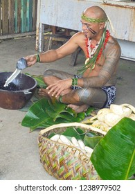 Apia / Samoa - 04 09 2017: polynesian man with traditional samoan tattoo showing how to make coconut milk in Samoan Cultural Village in capital city Apia, Upolu island, South Pacific, Oceania