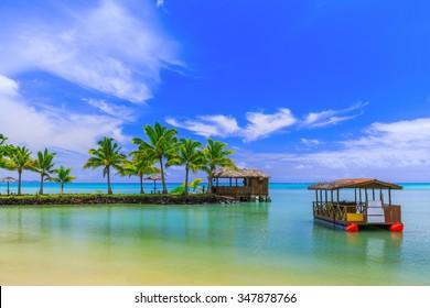 Apia, Samoa. Hut and boat by the beach.