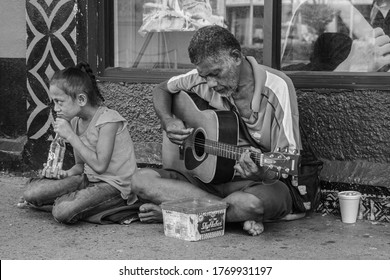 Apia, Samoa, March 10 2019: A busker plays on the street for money with his daughter next to him