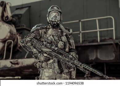Apocalypse. An armed man in chemical protection stands near an iron structure.