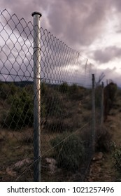 Apocalyptic scene of barbed wire fence and cloudy sky