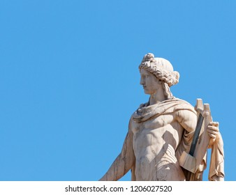 Apollo statue, the ancient greek god of music and poetry, blue sky as space for text