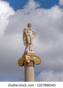 Apollo statue the ancient Greek god of music and poetry under cloudy sky, Athens Greece