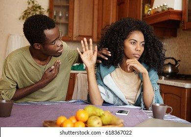 Apologetic African American male holding hand on his chest trying to convince mad woman in his fidelity. Black female ignoring her unfaithful husband's excuses. Love and relationships problems