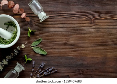 Apothecary of natural wellness and self-care. Herbs and medicine on dark wooden background top view frame copy space