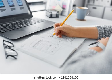 app design, technology and business concept - web designer or developer working on user interface and drawing sketches at office