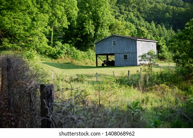 an Appalachian house sits in a cleared field in the mountains of western North Carolina.  The home is surrounded by lush green hills and forests.